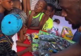 Usain Bolt dá uma de Papai Noel e distribui presentes para crianças de sua cidade natal