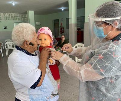 Após vacinação, idosa pede aplicação de imunizante para boneca, em asilo da Paraíba