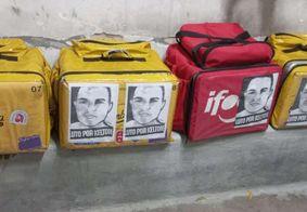 Cartazes foram colados em mochilas térmicas.